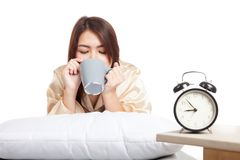 Happy Asian girl  wake up drink coffee with alarm clock Stock Image