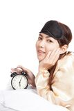 Happy Asian girl wake up with eye mask  and alarm clock Stock Photography