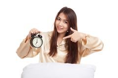 Happy Asian girl wake up point to alarm clock. Isolated on white background stock photography