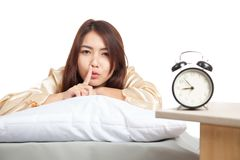 Happy Asian girl  wake up show quiet sign  with alarm clock Royalty Free Stock Image