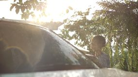 Happy Asian girl washing car on water splashing and sunlight at home stock footage