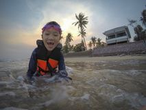 Happy asian girl wear life jacket and diving glasses,enjoy playing in the sea by the beach,tourist attractions at Kui Buri, royalty free stock photography