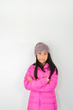 Happy Asian girl wearing pink down jacket sitting on gray. Background Royalty Free Stock Photo