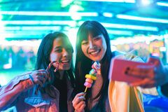 Free Happy Asian Girls Eating Candy Sweets And Taking Selfie At Amusement Park - Young Trendy Friends Having Fun With Technology Trend Stock Photo - 176899640