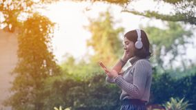 Happy Asian girls are listening to music. In the park stock photos