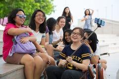 Happy Asian girls taking selfie in Singapore Stock Photo