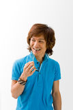 Happy Asian guy. Smiling Asian guy in blue t-shirt holding sunglasses and biting on it, isolated stock photos