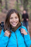 Happy Asian hiker girl in forest with backpack. And hiking poles walking with group of friends. Healthy smile Chinese woman tourist royalty free stock images