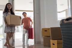 Asian couple move to new house. Happy Asian husband carry luggage and walk into new house while female wife carry box. moving with many boxes and luggage. First Stock Photography