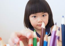 Happy asian kid girl selecting color pencil for drawing picture. Child looking for a green color Stock Photo