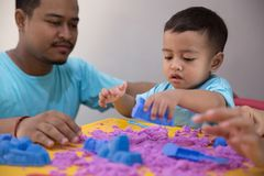 Asian kid play sand indoor. Happy asian kid play sand indoor with his parent Royalty Free Stock Photography