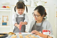 Asian Kid and young mother decorating cookies. royalty free stock photography