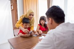 Kids play card game together. Happy asian kids play card game together with parent at home stock image