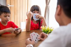 Kids play card game together. Happy asian kids play card game together with parent at home stock photo