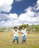 Happy asian kids running. On the grass Stock Photography