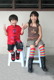 Happy Asian Kids Sitting on Stools. Two happy, smiling Asian children, sitting on stools, enjoy celebrating Chinese New Year.  Children are brother and sister Stock Photo