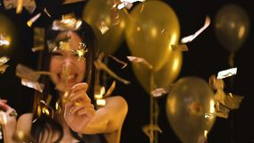 Happy Asian lady holding bengal light under falling confetti, party decoration. Stock footage stock video