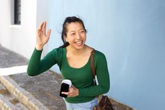 Happy asian lady outdoors on street gesturing for a taxi Stock Photography