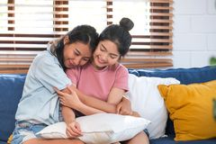 Happy asian lesbian couple hug each other with love on sofa at living room at home,LGBTQ lifestyle concept.  stock photo