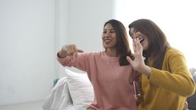 Happy Asian lesbian lgbt couple enjoy entertainment in living room. Beautiful women lying on a sofa listen to music on smartphone. Happy Asian lesbian lgbt stock footage