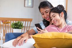 Happy asian lesbian watching video on mobile phone at sofa in house.LGBTQ lifestyle concept.  stock images