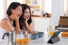 Happy asian lesbian woman couple video chat with friend in breakfast time at house in morning with love and tender.LGBTQ lifestyle. Happy asian lesbian women royalty free stock photos