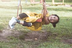 Happy asian little child girl having fun to play on swing Stock Photos