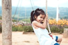 Happy asian little child girl having fun to play on wooden swings. In playground at the garden Royalty Free Stock Photo