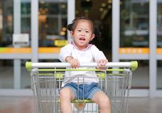 Happy Asian little child girl sitting in the trolley during family shopping in the market stock photography