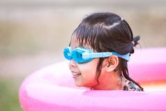 Happy asian little child girl wearing swimming goggles royalty free stock photo