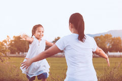 Happy asian little child girls running to their mother. To give a hug with love in the park in vintage color tone stock image