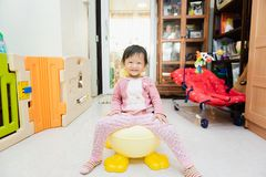 Happy Asian little child sitting on small flush toilet. At home after wake up in morning royalty free stock image