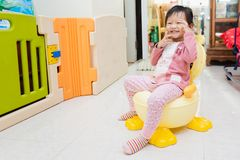 Happy Asian little child sitting on small flush toilet at home after wake up. In morning royalty free stock images