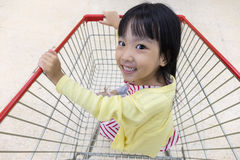 Happy Asian Little Chinese Girl sitting in shopping cart Stock Photo