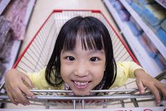 Happy Asian Little Chinese Girl sitting in shopping cart Royalty Free Stock Photos