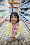 Happy Asian Little Chinese Girl sitting in shopping cart Royalty Free Stock Image