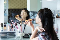 Happy asian little girl, adding some color to my cheeks and applying foundation powder or blush with makeup brush,side view of ch royalty free stock photo