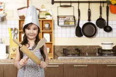 Happy asian little girl with chef hat holding cooking appliance. In the kitchen room Stock Photos
