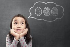 Happy asian little girl dreaming to hunt easter eggs. On blackboard background stock photos