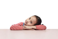 Happy asian little girl lying down on the desk Royalty Free Stock Image