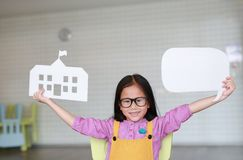 Happy Asian little girl in pink-yellow dungarees holding mock-up paper school and empty blank speech bubble to tell something in. Classroom with looking royalty free stock photography