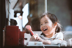 Happy asian little girl playing and talking phone in cafe Stock Photos