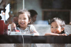 Happy asian little girl playing and talking phone in cafe Stock Photo