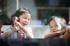 Happy asian little girl playing and talking phone in cafe Royalty Free Stock Photos