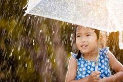 Happy asian little girl with umbrella in rain. In vintage color tone Royalty Free Stock Photography