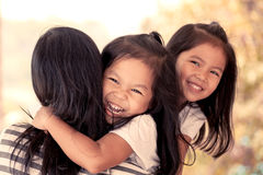 Happy asian little girls hugging mother Stock Photo