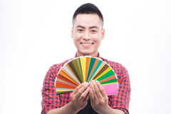 Happy asian male graphic designer holding color fan in his hand.  stock photography