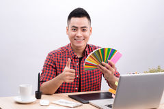 Happy asian male graphic designer holding color fan in his hand.  royalty free stock photography