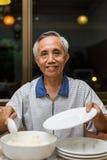 Happy Asian male senior serving rice Stock Photos