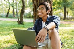 Happy asian male student in eyeglasses with laptop computer stock photography
